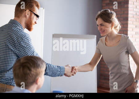 Millennial male worker handshaking female partner or colleague - Stock Photo
