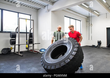 Fit young man with a personal trainer in gym working out, moving large tire. - Stock Photo