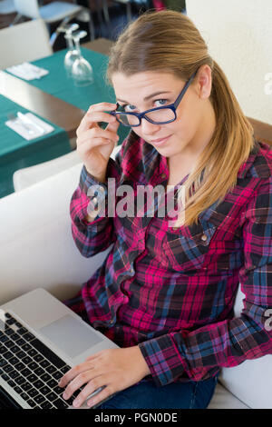young girl with laptop looking at camera in the bar - Stock Photo