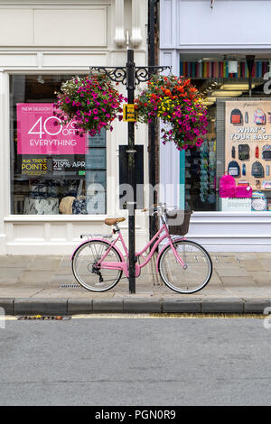 Pink ladies bicycle chained to post on pavement - Stock Photo