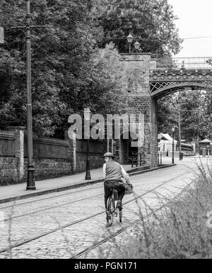 Nostalgic, black & white, rear view portrait shot of lone 1940's style male cyclist in tin helmet riding along deserted, cobbled street looking back. - Stock Photo