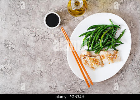 Fish fillet served with soy sauce and green beans in white plate. Asian food. Top view. Flat lay - Stock Photo