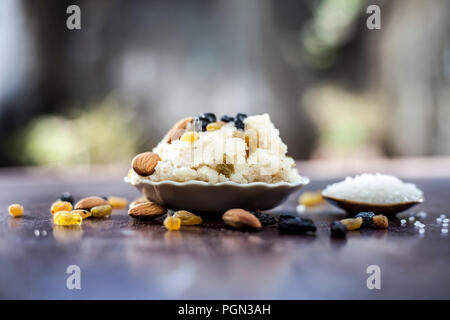 Popular Indian and Asian dessert Suji ka halwa or Rava with organic almonds, cashews and black & golden raisns in a clay bowl on wooden surface. - Stock Photo