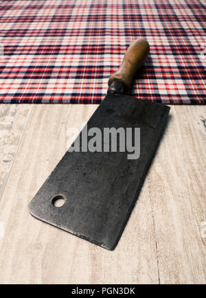 Old meat cleaver on a rustic kitchen table - Stock Photo