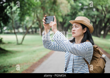 Asian woman backpack traveler use mobile take photo when traveling at rain forest.Holiday vacation concept.journey lifestyle.solo travel - Stock Photo
