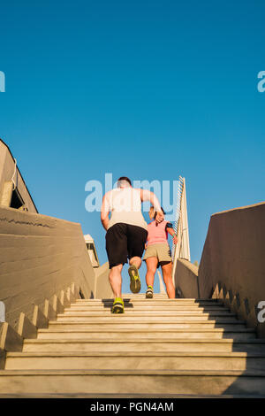 Fitness couple jogging upstairs at urban place - Stock Photo