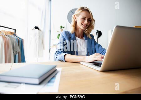 Fashion designer working on her designs in the studio - Stock Photo