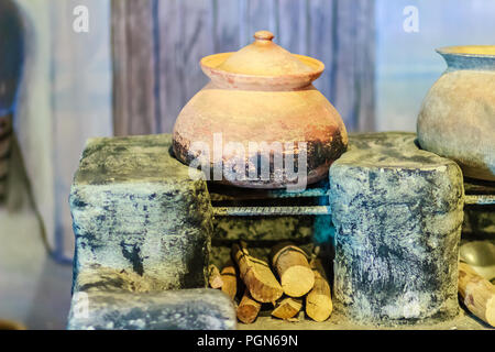Vintage local kitchen area with old porcelain pot on the antique stove and firewood - Stock Photo