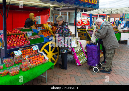 Elderly customers at a greengrocer and fruiterers market stall in Redcar Town Centre - Stock Photo