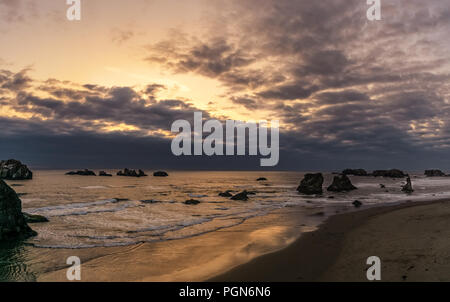 Bandon Beach at sunset with dramatic colorful sky from the Face Rock Scenic Viewpoint, Oregon Coast, USA. - Stock Photo