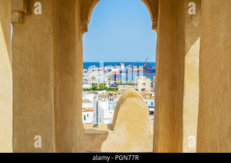 The small window in tower of Ribat fortress overlooks the roofs of Medina and industrial port, Sousse, Tunisia. - Stock Photo