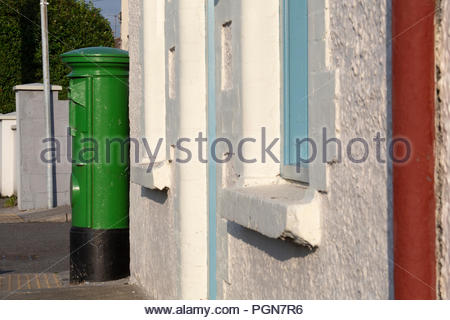 A green irish post box in brilliant sunshine in Tralee County Kerry - Stock Photo