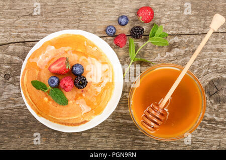 Pancakes stack with different berries and honey on old wooden background. Top view. Flat lay - Stock Photo