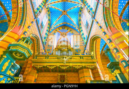 KRAKOW, POLAND - JUNE 11, 2018: The choir and organ located above the main entrance to the St Mary Basilica and decorated with carved elements and gil - Stock Photo
