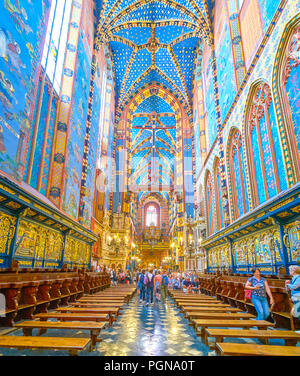 KRAKOW, POLAND - JUNE 11, 2018: The narrow chancel of St Mary Basilica decorated with gilden bas-reliefs above prayers sits and painted walls, on June - Stock Photo