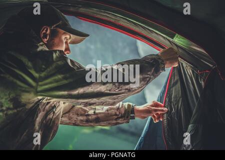 Game Hunter Camping Spot. Caucasian Hunting Men in His 30s Closing His Tent From Inside. - Stock Photo