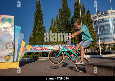 A guy riding a bicycle on Lenin Square in the center of Tambov city, Russia - Stock Photo