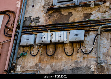 Electricity meters numbered on old cracked walls - Stock Photo