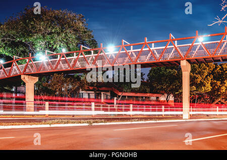 Red pedestrian bridge above the street. Light trails from the cars passing on the street. Red bridge at night of the Horto Florestal in Campo Grande M - Stock Photo