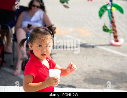 Asian toddle in pigtails dressed in red walking holding plastic cup - Stock Photo