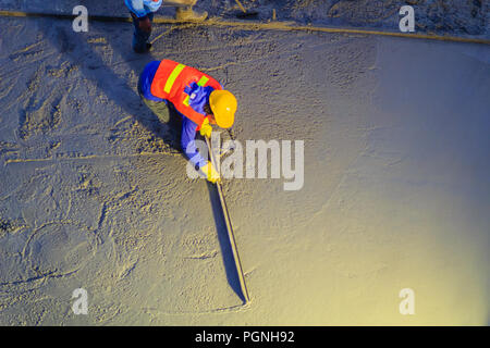 Mason worker leveling concrete with trowels, mason hands spreading poured concrete. Concreting workers are leveling poured liquid concrete on a steel  - Stock Photo
