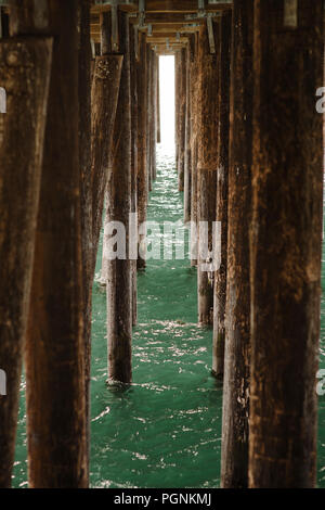 Light peers through wooden pylons under a pier - Stock Photo