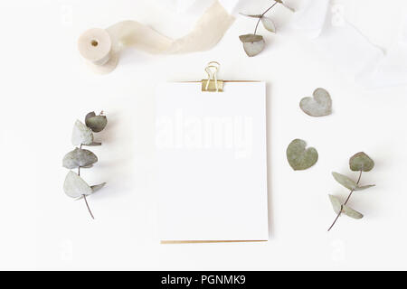 Feminine wedding desktop stationery mockup with blank greeting card, dry eucalyptus leaves, silk ribbon and golden binder clip on white table background. Flat lay, top view. Styled stock photo. - Stock Photo