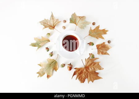 Autumn maple and oak leaves composition with cup of tea and acorns on white background. Styled stock photo. Flat lay, top view. Fall design. - Stock Photo