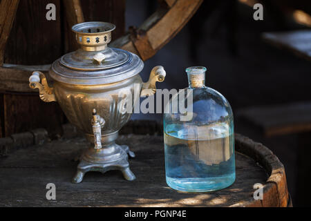 Bottle of moonshine on a wooden barrel close-up - Stock Photo