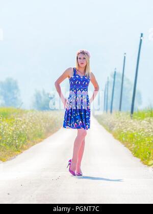 Young woman legs heels blonde strike pose on long road ladylike - Stock Photo