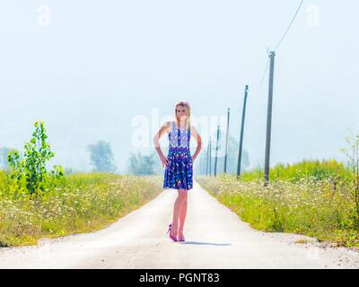 Young woman legs heels blonde strike pose on long road - Stock Photo