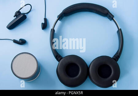 Wireless headset, wired headset, speaker isolated on pastel blue background. Top view, flat lay. - Stock Photo