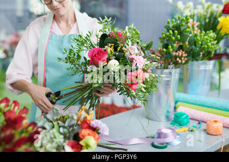 Crop view of smiling woman arranging flower bouquet in shop - Stock Photo