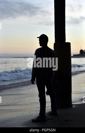 Silhouette of a man overlooking the ocean from under the pier - Stock Photo