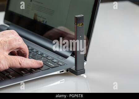 JUUL nicotine dispenser beng charged in laptop - Stock Photo