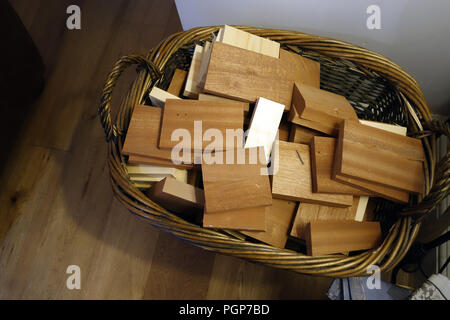 Basket of hardwood off cuts of wood ready for the log fire - Stock Photo