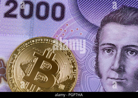 A close up image of a 2000 Chilean peso bill with a golden physical bitcoin - Stock Photo