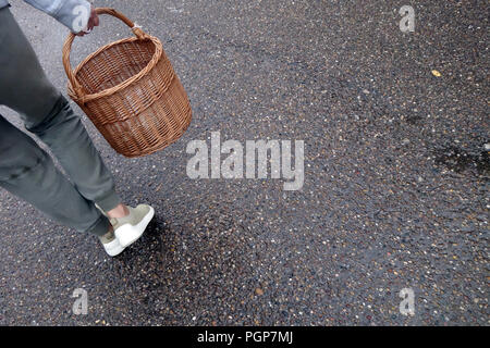 lower half of a woman walking with a woven basket on wet outdoor path - Stock Photo