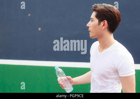 man holding clean bottle of fresh mineral  drinking water outdoor under summer heat. Health care, Well being, Thirst Refreshment, Water Balance in bod - Stock Photo