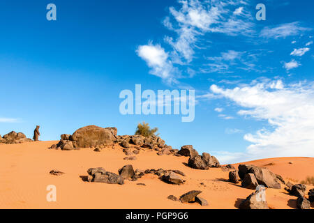 Erg Chebbi, Morocco. Old man wearing a djellaba robe stands by some boulders in the sand and looks into the distance. Blue sky. Copy space - Stock Photo