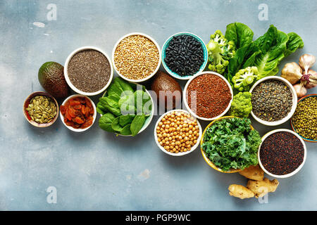 Vegetarian healthy food concept. Set raw seeds, cereals, beans, superfoods and green vegetables on blue stone background top view flat lay - Stock Photo