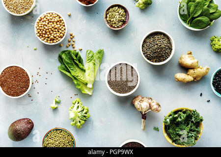 Set raw seeds, cereals, beans, superfoods and green vegetables on blue stone background top view. vegetarian or diet food concept - Stock Photo