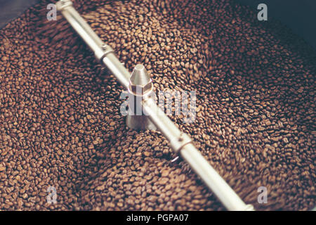The freshly roasted coffee beans from a large coffee roaster being poured into the cooling cylinder. Motion blur on the beans. - Stock Photo