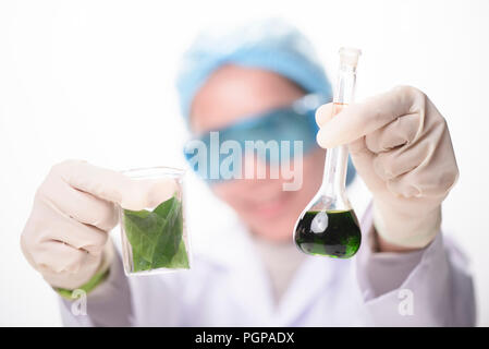 Scientist hand holding green leaf in glass cuvette on laboratory. biotechnology concept. - Stock Photo