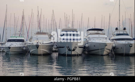 Five boats moored in Split harbour at early evening, on the water with boat masts behind - Stock Photo