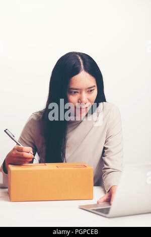 startup small business owner working with computer at workplace. freelance woman seller check product order, packing goods for delivery to customer. O - Stock Photo