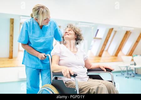 Caring caregiver takes care of a senior woman in a wheelchair at rehab - Stock Photo