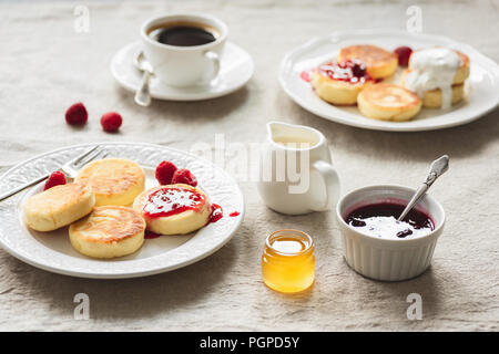 Breakfast Table With Curd Fritters or Pancakes, Coffee, Jam and Honey. Russian, Ukrainian cuisine. Cozy breakfast or comfort food concept