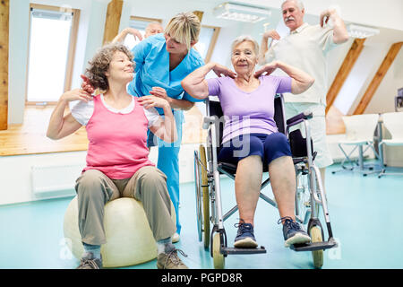 Senior group is doing a back exercises course with coach supervision - Stock Photo