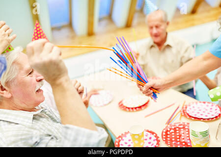 Seniors celebrate together a birthday party in the retirement home with care - Stock Photo